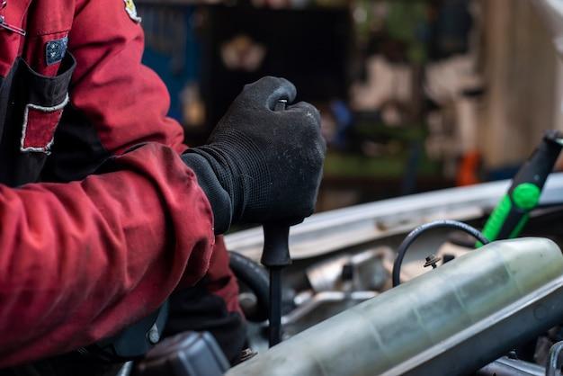 Ręka mechanika przy pracy nad silnikiem w warsztacie
