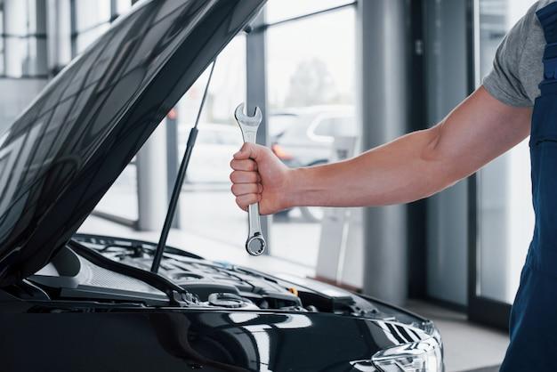 Ręka mechanika samochodowego z kluczem w strefie kombi w pobliżu samochodu w warsztacie.