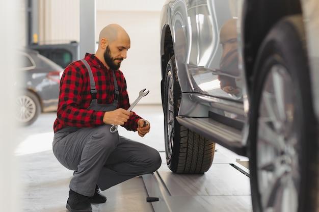 Ręka mechanika samochodowego z kluczem w strefie kombi w pobliżu samochodu w warsztacie