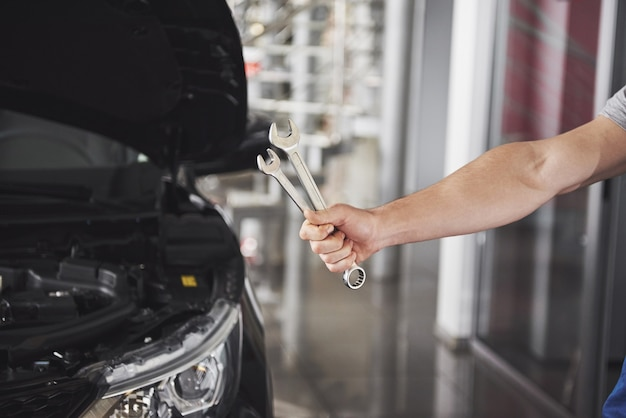 Ręka mechanika samochodowego z kluczem. warsztat samochodowy.