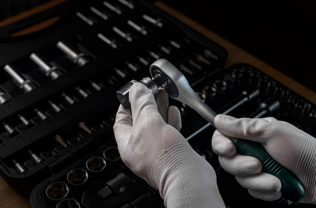 Ręka mechanika w białej rękawiczce z grzechotką nasadową i metalowym stalowym sześciokątnym gniazdem, zbliżenie. narzędzia metalowe do naprawy samochodów.