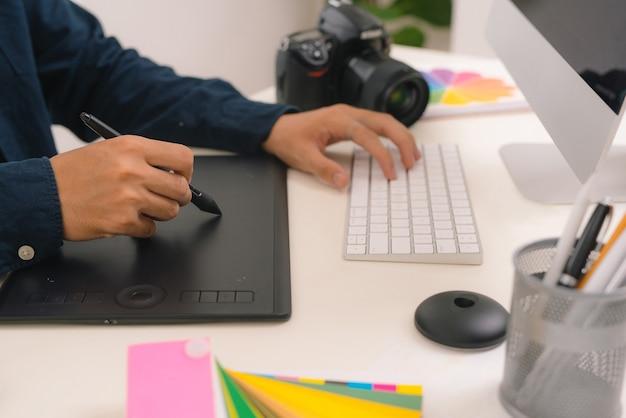 Ręka męskiego projektanta pracującego przy biurku za pomocą rysika i cyfrowego tabletu graficznego.