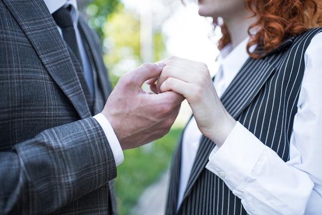 Ręka męża trzyma rękę rudej żony w naturze z bliska