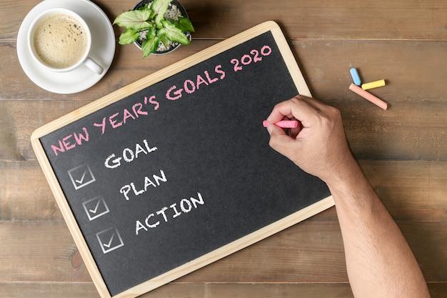 Ręka mężczyzna pisze nowy rok celów 2020 tekstem na czarnej desce.