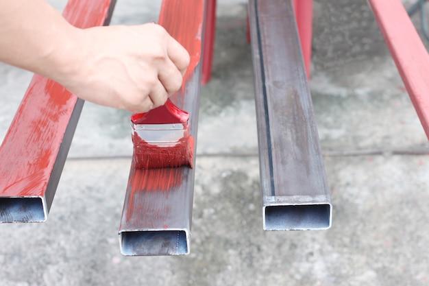 Ręka mężczyzna pracownik trzyma paintbrush malował stal dla przemysłowego.
