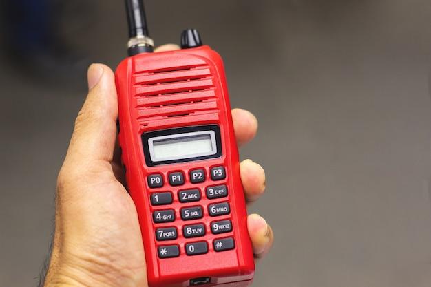 Ręka mężczyzna trzyma czerwonego walkie talkie