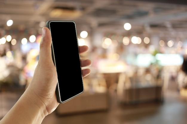 Ręka mężczyzna trzyma mądrze telefonu przyrząd w kawowej kawiarni