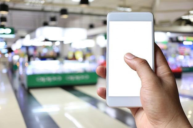 Ręka mężczyzna trzyma smartphone przyrząd w zakupy centrum handlowym.