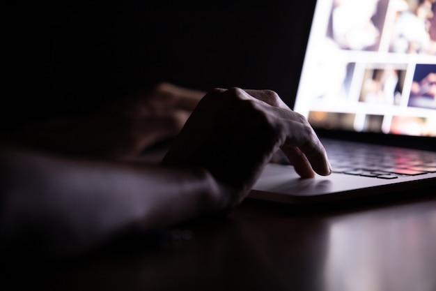 Ręka mężczyzna używa laptop pracuje przy nocą