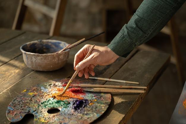 Ręka mężczyzny bierze pędzel ze stołu, na którym leżą narzędzia do rysowania