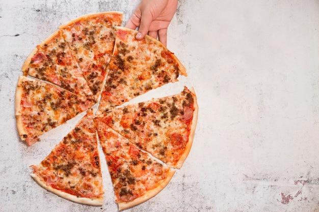 Ręka mężczyzny biorąc kawałek pizzy. białe kamienne tło i miejsce na tekst
