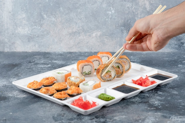 Ręka mężczyzny biorąca panierowaną gorącą bułkę sushi z pałeczkami