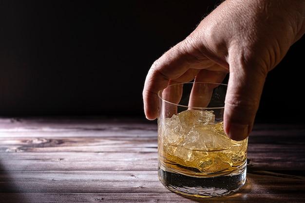 Ręka mężczyzny biorąca szklankę z whisky lub szkocką i dużymi kawałkami lodu na rustykalnym drewnianym stole