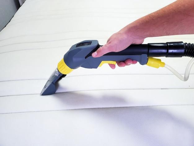 Ręka mężczyzny czyści nowoczesny biały materac profesjonalnym środkiem czyszczącym.