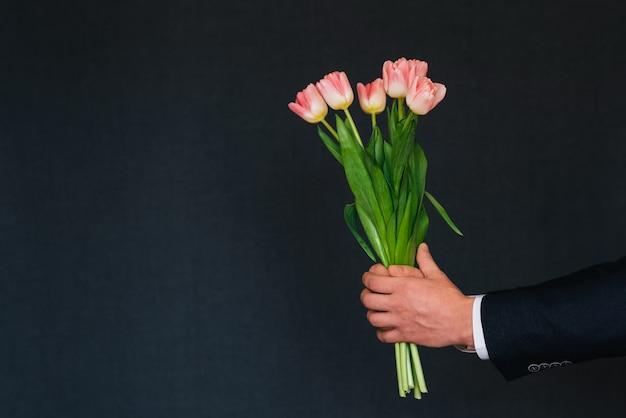 Ręka mężczyzny, dając bukiet różowych tulipanów