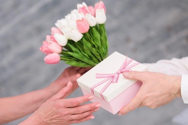 Ręka mężczyzny dając prezent urodzinowy i bukiet kwiatów tulipanów do jego żony