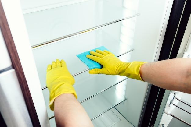 Ręka mężczyzny do czyszczenia białej lodówki z niebieską szmatką