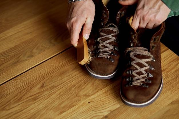 Ręka mężczyzny do czyszczenia zamszowych butów za pomocą szczotki na drewnianej podłodze