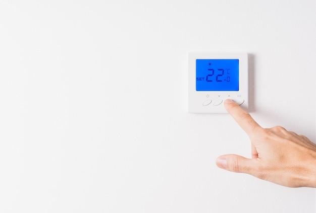 Ręka mężczyzny dostosowująca temperaturę białego termostatu do dwudziestu dwóch stopni z podświetlanym na niebiesko wyświetlaczem na białej ścianie