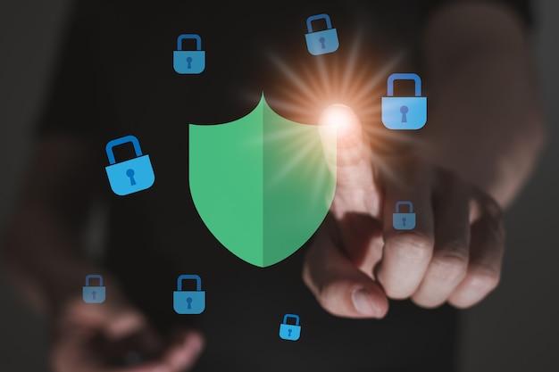 Ręka mężczyzny dotyka ikony bezpieczeństwa z grafiką komputerową i niebieską ikoną kłódki, technologia cyberochrony internetowej, koncepcja bezpieczeństwa centrum danych