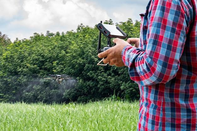 Ręka mężczyzny drona rolniczego leci rozpylać nawóz na polach trzciny cukrowej. rolnictwo przemysłowe i technologia dronów inteligentnego rolnictwa.