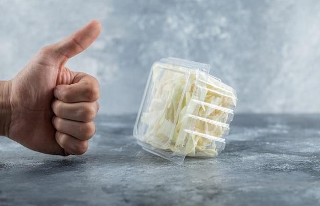 Ręka mężczyzny gestykuluje kciuk do świeżego sera. wysokiej jakości zdjęcie
