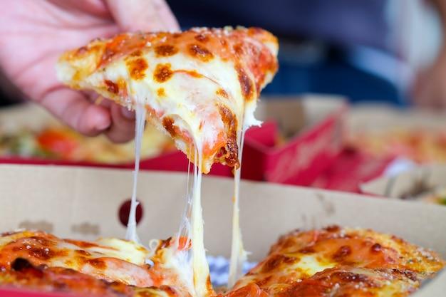 Ręka mężczyzny gospodarstwa pizza z pudełka