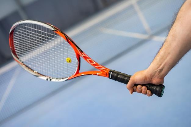 Ręka mężczyzny gospodarstwa rakieta tenisowa na korcie tenisowym