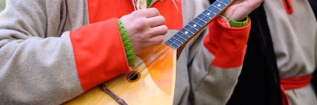 Ręka mężczyzny gra na bałałajce. muzyk z tradycyjnym rosyjskim instrumentem muzycznym w zimowych rosyjskich strojach ludowych.