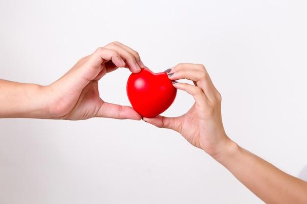Ręka mężczyzny i kobiety dłoń trzymająca czerwone serce.