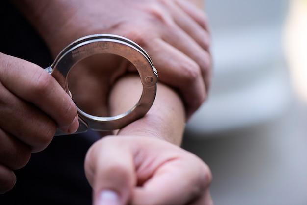 Ręka mężczyzny jest zamknięta kajdankami