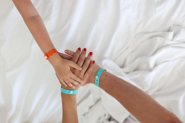 Ręka mężczyzny, kobiety i dziecka trzymają się razem jeden na drugim