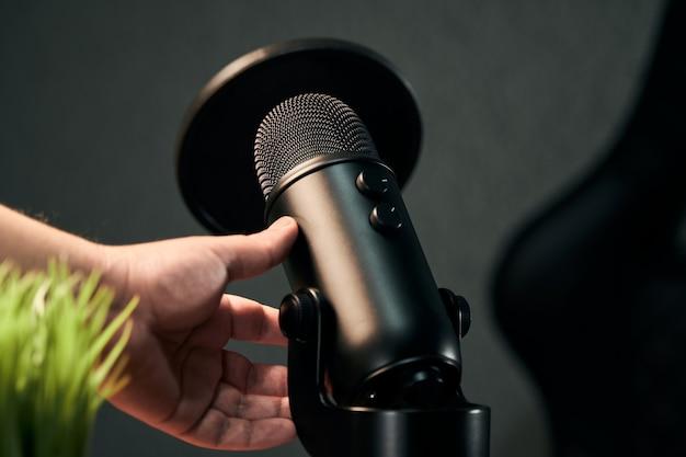 Ręka mężczyzny, który ma zamiar wziąć czarny mikrofon na ciemnoszarym