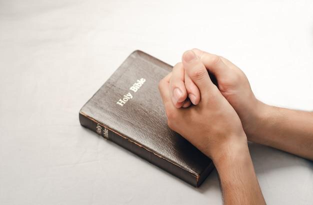 Ręka mężczyzny, który modlił się zgodnie z biblią w wierze chrześcijańskiej