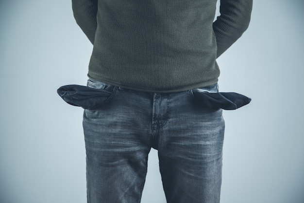 Ręka mężczyzny na pustej kieszeni na szarym tle