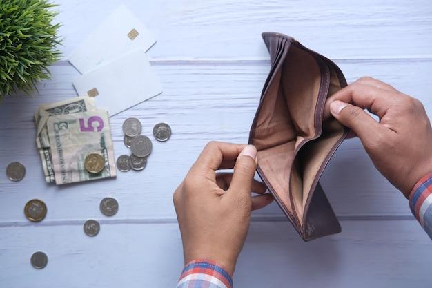 Ręka mężczyzny otwiera pusty portfel z miejscem na kopię