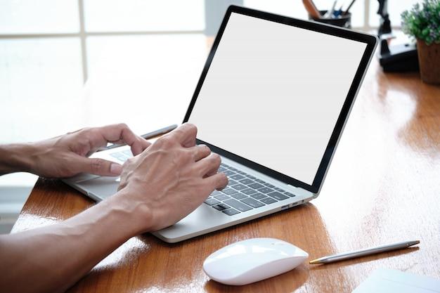 Ręka mężczyzny pisze klawiaturę na laptopie.