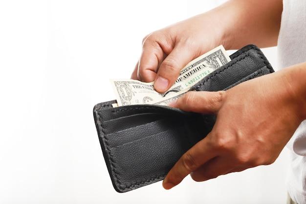 Ręka mężczyzny podnosi banknoty dolarowe z czarnego skórzanego portfela, płaci gotówką za zakupy. kieszonkowe na codzienne wydatki