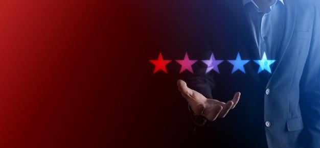 Ręka mężczyzny pokazująca na pięć gwiazdek ocena doskonała
