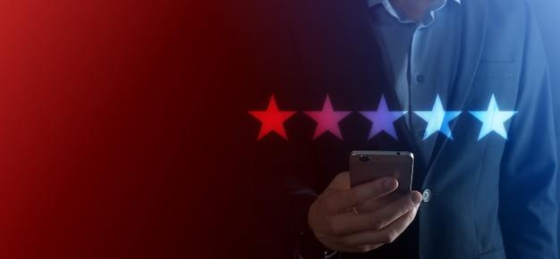 Ręka mężczyzny pokazująca na pięciogwiazdkowej doskonałej ocenie. wskazując pięciogwiazdkowy symbol, aby zwiększyć ocenę firmy. przejrzyj, zwiększ ocenę lub ranking, koncepcję oceny i klasyfikacji.