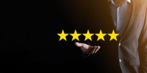 Ręka mężczyzny pokazująca pięciogwiazdkową ocenę doskonałą. wskazanie symbolu pięciogwiazdkowego w celu zwiększenia oceny firmy. przegląd, zwiększenie oceny lub rankingu, koncepcja oceny i klasyfikacji.