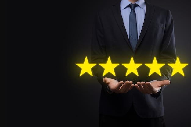 Ręka mężczyzny pokazująca pięciogwiazdkową ocenę doskonałą. wskazanie symbolu pięciu gwiazdek w celu zwiększenia oceny firmy.
