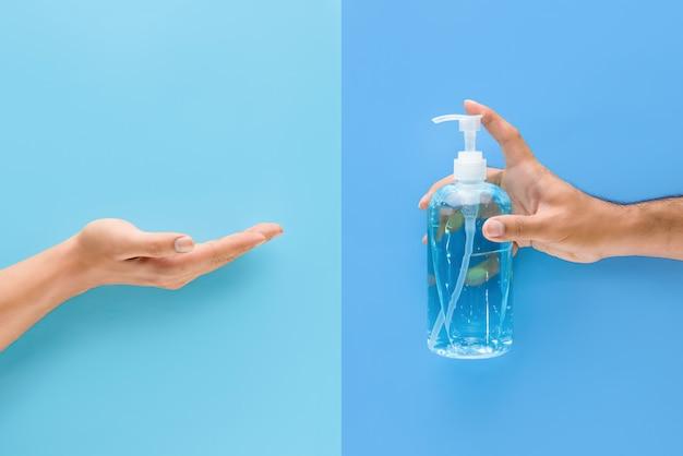 Ręka mężczyzny pompująca żel alkoholowy do drugiej ręki w celu oczyszczenia i ochrony przed zarazkami i wirusami