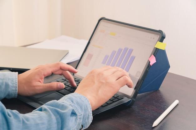 Ręka mężczyzny pracująca z cyfrowym tabletem na stole biurowym sprawia, że podsumowanie informacji raportu biznesowego wykresu finansowego.