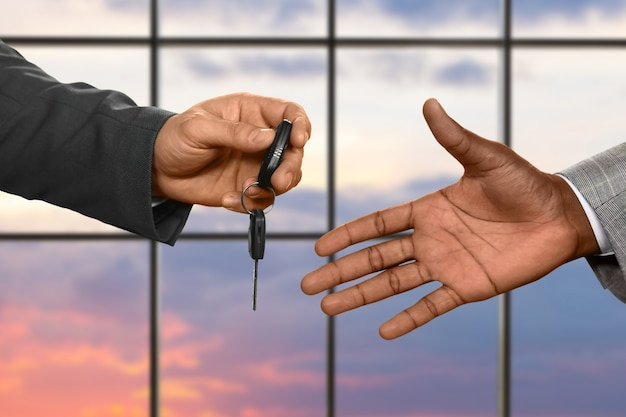 Ręka mężczyzny przekazująca kluczyk do samochodu. klucz samochodowy na tle wschodu słońca. zawsze jedź bezpiecznie. luksus nie jest dla każdego.