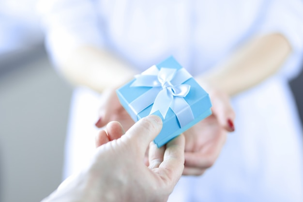 Ręka mężczyzny przekazuje pudełko niespodziance kobiecie dla koncepcji kobiety