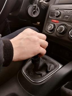 Ręka mężczyzny przełącza zbliżenie ręcznej skrzyni biegów