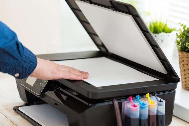 Ręka mężczyzny robi kopie. praca z drukarką