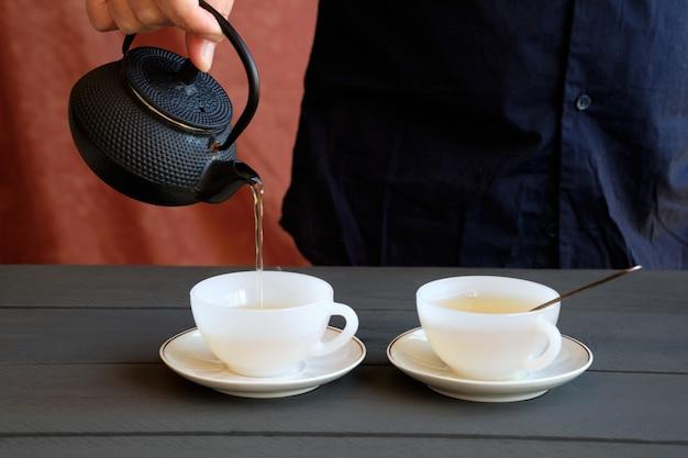 Ręka mężczyzny serwująca dwie filiżanki zielonej herbaty