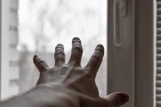 Ręka mężczyzny sięga do okna. koncepcja: proszenie o pomoc, depresja, szukanie wyjścia, wolność, dzielenie się swoimi uczuciami. ręka na tle oświetlonego okna.